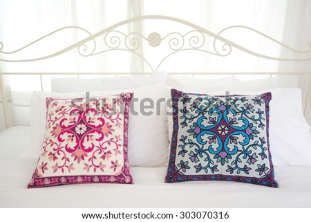Bed with white linen and colorful pillows. Vintage Interiors. - stock photo