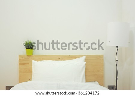 Bed with white linen beside the lamps. Minimalism interior.