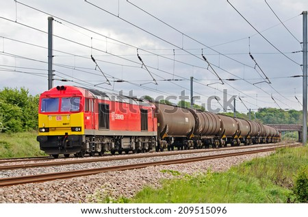 BEDFORD, UK - MAY 2: A DBS hauled oil train passes  through Bedfordshire on route to Lindsey oil refinery May 2, 2014 in Bedford. Lindsey refinery is owned by Total SA and employs 500 personnel - stock photo
