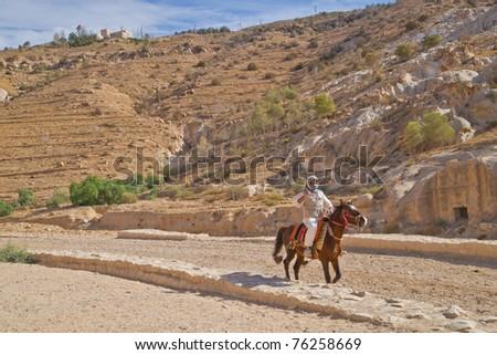 Bedouin horseman rides the ancient roadway into Petra, Jordan - stock photo