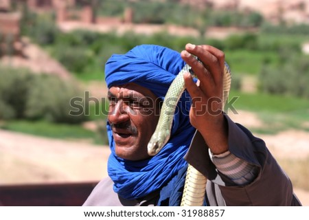 bedouin in morocco with snake in front of ancient village of ait benhaddou