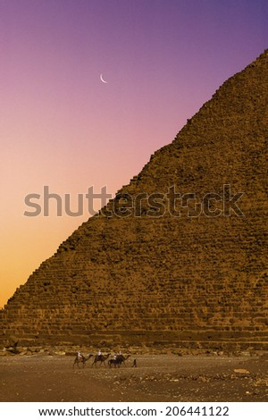 Bedouins on camels against the pyramid in Egypt - stock photo