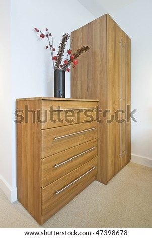Bedroom detail with large wooden wardrobe, chest of drawers and decorative flowers - stock photo