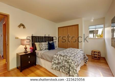 Bedroom furniture with mocha tone bedding. Room has closet - stock photo