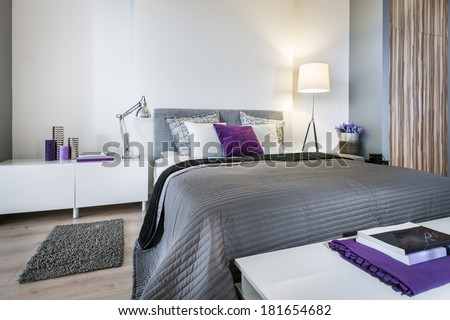 Bedroom interior with gray bed and white walls - stock photo