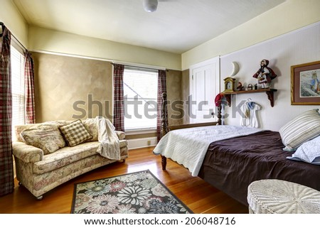 Bedroom interior with hardwood floor and rug. Furnished with high pole bed and floral sofa