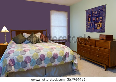 bedroom interior with purple and green walls lamp dresser colorful pillows and comforter decorating queen size bed  - stock photo