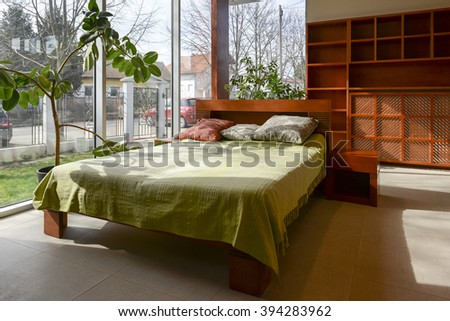 Bedroom interior with wooden master bed - stock photo