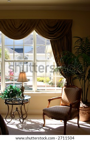 bedroom seating area in sunlight overlooking swimming pool in upscale home - stock photo