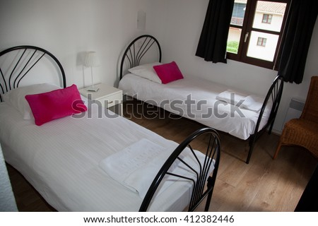 Bedroom, two beds with bedside table and white lamp. - stock photo