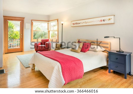 Bedroom with glass door, red leather chair and wooden floor. - stock photo