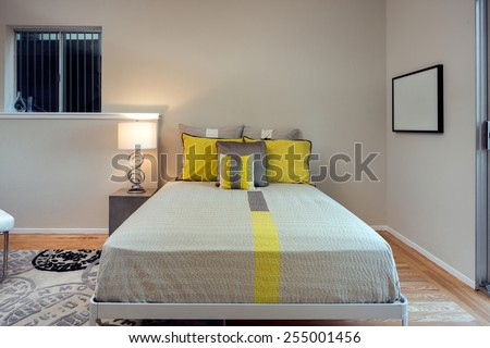 Bedroom with grey yellow sheets, pillows, night stands and natural fibers rug. - stock photo