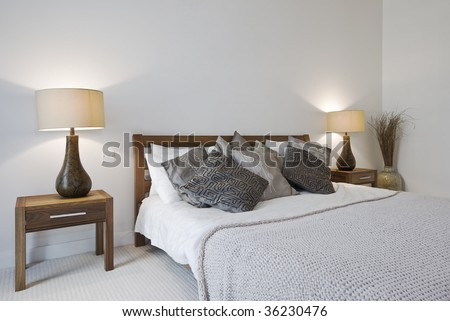 bedroom with king size bed bedside tables and reading lamp - stock photo