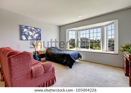 Bedroom with large window and small bed with armchair and art.