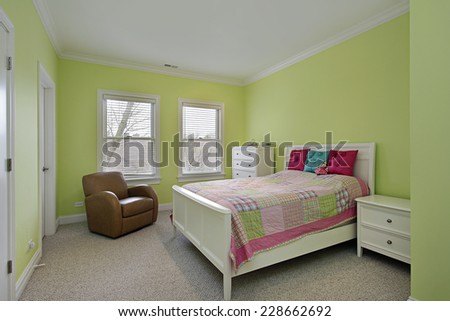 Bedroom with lime green walls and plaid bedspread - stock photo