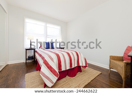 Bedroom with red white bed sheets with night stands and natural fibers rug - stock photo