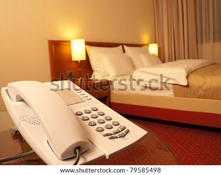 bedroom with telephone in front and bed in the background, focus on the telephone,for room service,communication themes - stock photo