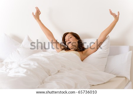 Bedroom - woman waking up and stretching in white bed - stock photo