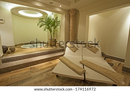 Beds and jacuzzi in a private VIP area of luxury health spa - stock photo