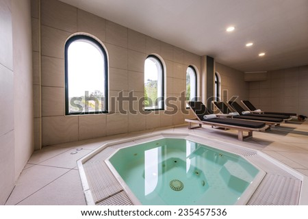 Beds and jacuzzi in luxury health spa - stock photo