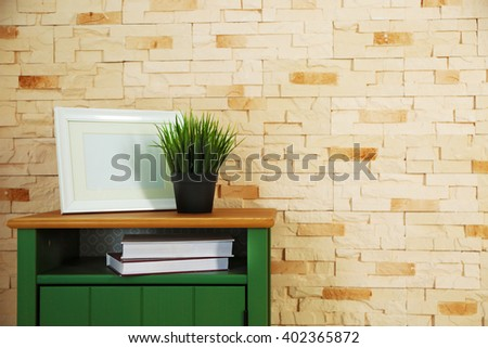 Bedside-table and home decor on a brick wall background - stock photo