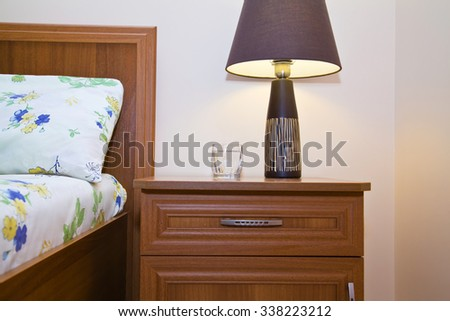 Bedside table with lamp glowing  closeup in  bedroom near the bed