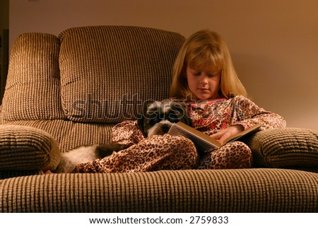 Bedtime Reading: A young girl in her pajamas sits on a comfy chair in cozy lighting with a good book and her faithful dog. - stock photo