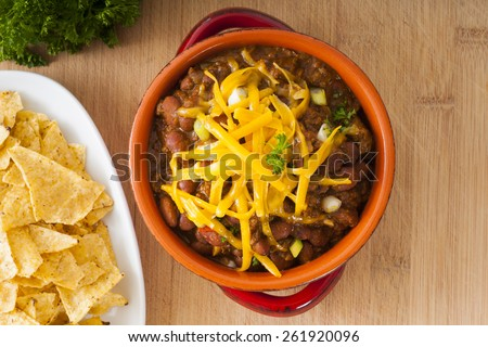 Beef and bean mexican chili with nacho chips and cheddar cheese - stock photo