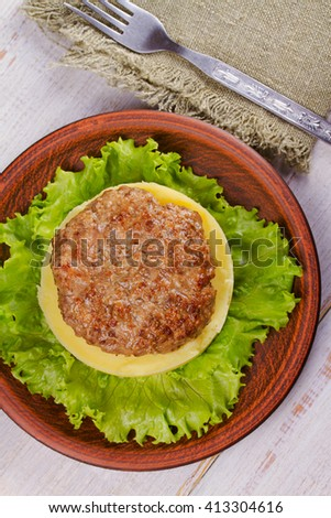 Beef and pork patty with smashed potato and lettuce. View from above, top studio shot