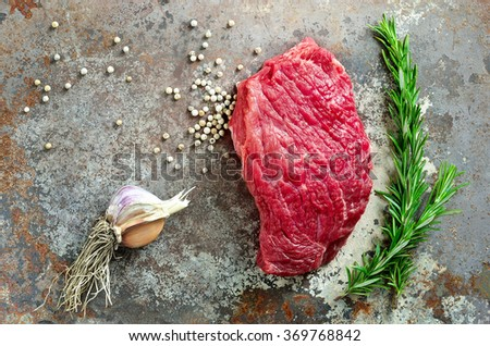 Beef and spices, raw steak with pepper, garlic and rosemary, view from above - stock photo