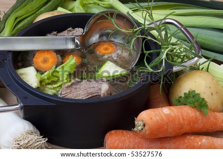 Beef boiled in pan with carrot, leeks, celery and spices for beef soup, ready to serve. - stock photo