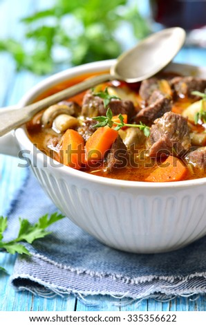 Beef Bourguignon in rustic bowl on turquoise wooden table. - stock photo