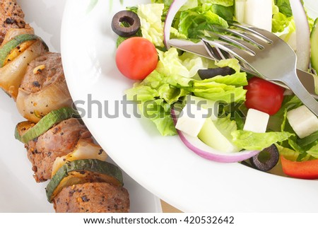 Beef brochette served with Greek salad - stock photo