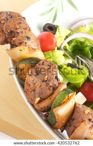 Beef brochette with Greek salad - stock photo
