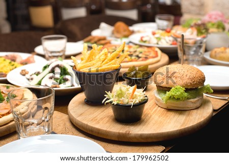 Beef burger and french fries on a table with other food plates in the background  - stock photo