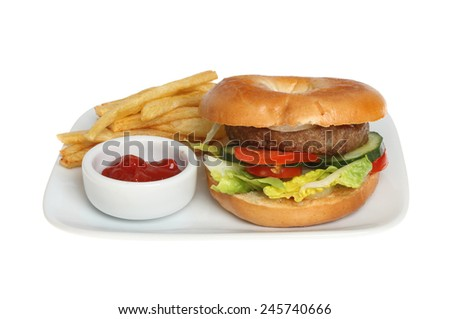 Beef burger in a bagel with fries and tomato ketchup on a plate isolated against white - stock photo