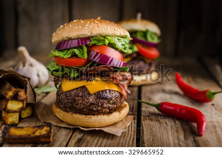 Beef burger rustic style, with chilli peppers and homemade french fries. - stock photo