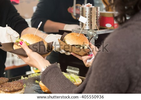 Beef burgers being served on food stall on open kitchen international food festival event of street food.