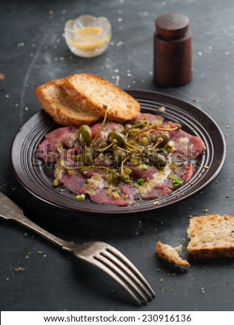 Beef carpaccio with capers on dark background, selective focus - stock photo