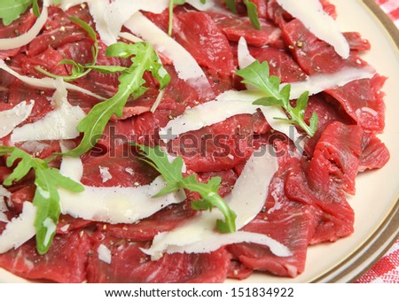 Beef carpaccio with Parmesan shavings and arugula. Shallow DoF.
