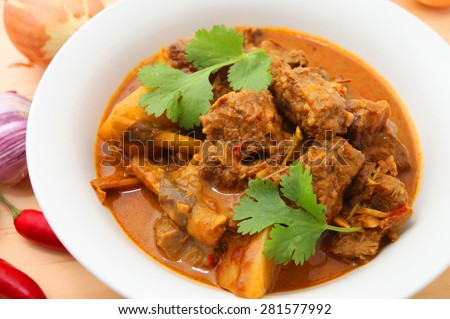 Beef Curry in a bowl on the wooden table with ingredients - stock photo