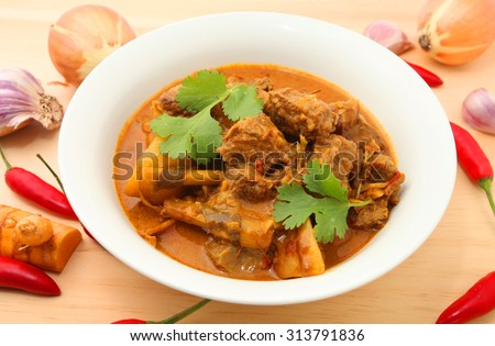 Beef Curry in a bowl on the wooden table with ingredients