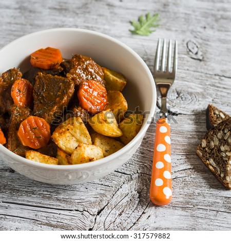 beef goulash with carrots and roasted potatoes in a white bowl on a light wooden background - stock photo