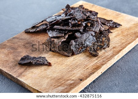Beef jerky on wood board. Stone cement background. Thin sliced jerked or sun-dried beef with spices is a classic spicy snack for beer in pubs and bars - stock photo