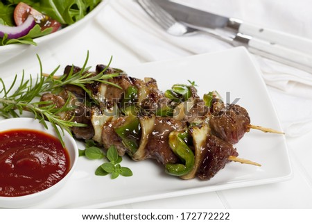 Beef kebabs with herbs and a green salad. - stock photo