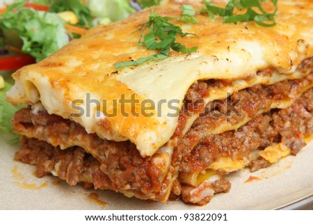 Beef lasagna with salad. Shallow DoF, focus to the right of image center. - stock photo