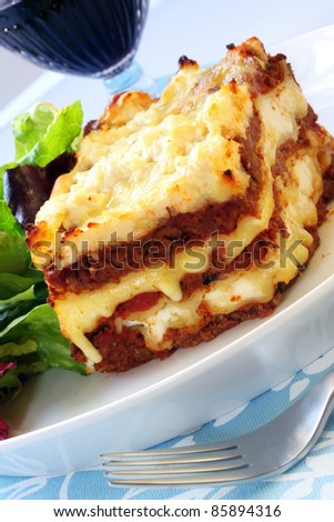 Beef lasagne with salad and red wine.  Delicious melting mozzarella and ricotta cheeses. - stock photo