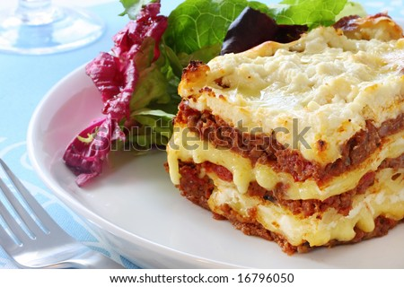 Beef lasagne with salad.  Melting mozzarella and ricotta cheeses - delicious! - stock photo