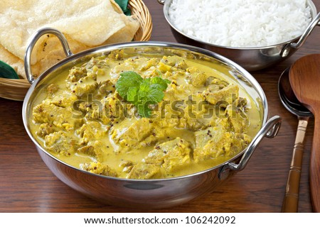 Beef Madras curry, made with lots of chilli, coconut and mustard seeds, served with poppadums and basmati rice. - stock photo