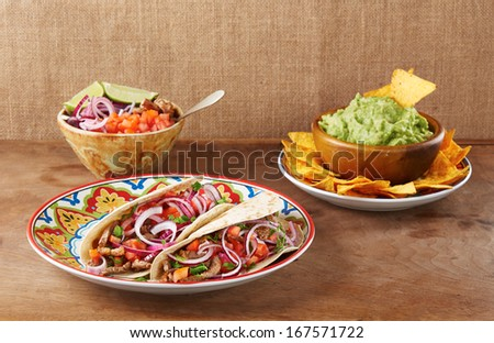 Beef meat and vegetables Mexican tacos with guacamole nachos - stock photo